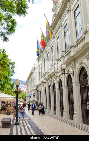 Funchal, Madeira, Portugal - Sep 10, 2019: Building of the theater in Madeiran capital - Teatro Municipal Baltazar Dias. People on the street in historical center. Tourist attractions. Waving flags. - Stock Photo