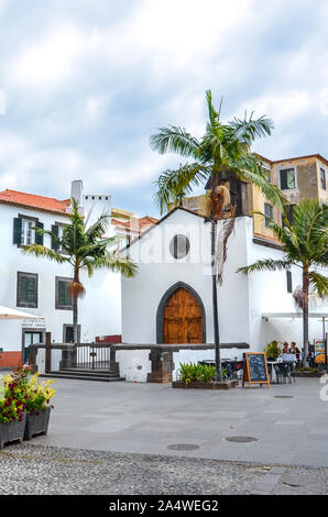 Funchal, Madeira, Portugal - Sep 10, 2019: Streets in Madeiran capital with typical colonial buildings. People drinking and eating on outdoor terraces. Palm trees. Historical old town. - Stock Photo