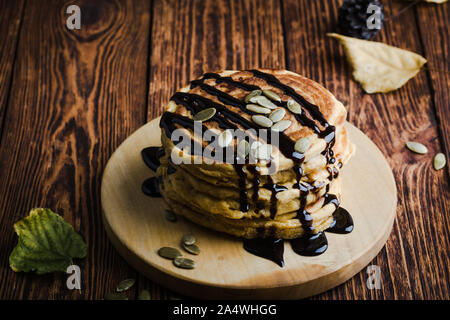 Pumpkin pancakes with chocolate, autumn dessert, Thanksgiving day breakfast or brunch, plant based meal - Stock Photo