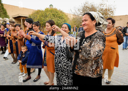 Dancing guests during a wedding in the main street of the old town of Khiva, a very popular site for all the festivities in the town. Uzbekistan - Stock Photo