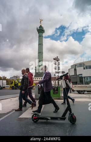 Paris, France - 3rd October, 2019:  Pedestrians walking by E-scooter at The Place de la Bastille  in central paris - Stock Photo