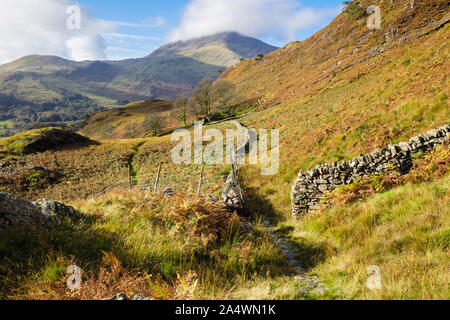 View along stone wall to Moel Hebog with low cloud from footpath above Nant Gwynant in hills of Snowdonia National Park in autumn. north Wales, UK