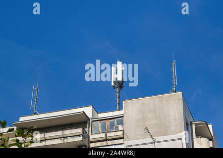 Antennas of cellular communication on a roof of a gray multi-storey residential building against blue sky. Low angle view. - Stock Photo