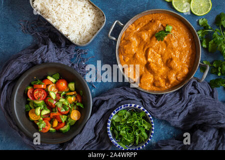 A colorful Indian curry dinner with Fresh salad flat lay seen from above. With lime, tomatoes, cucumber, cilantro, and rice. - Stock Photo