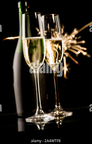 Two champagne glasses and bottle in front of fireworks on black background - Stock Photo