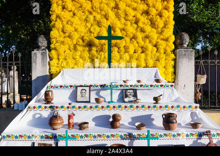 Merida, Mexico - 31 October 2018: Flower altar with cross and offerings for day of the dead, tradition for dia de los muertos in Calle 66 - Stock Photo