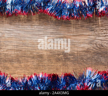 New Year, Christmas background with copy space. Old wooden boards framed by blue tinsel - Stock Photo