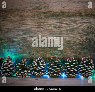 New Year's background. Fir cones, blue tinsel and lights garland on a old barn boards. Tinted photo - Stock Photo