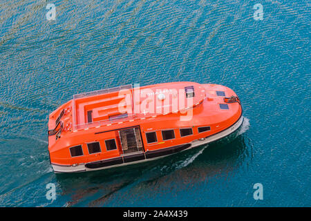 A tender is carrying passengers from a cruise liner to Olden pier on the Innvikfjorden in Norway with Olden Fjordhotel right - Stock Photo