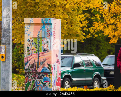 Hand painted design on a traffic signal box in the city of Toronto in autumn, with yellow maple tree leaves above and below it. - Stock Photo