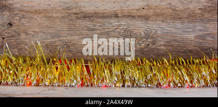 old wooden background with gold tinsel and garland with space for text. the concept of new year Christmas - Stock Photo