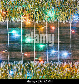 Festive Christmas New Year background. Multicolored Christmas lights garland and gold tinsel on the old barn boards - Stock Photo