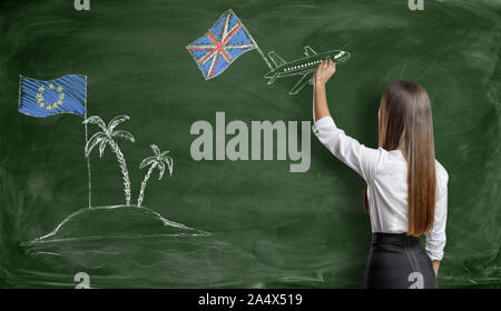 Businesswoman drawing plane with british flag that flies away from an EU island - Stock Photo