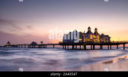 Pier in Sellin, the Jewel of Rugia (Ruegen) Baltic Coast island at purple sunrise, Germany. - Stock Photo