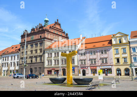 Plzen, Czech Republic - June 25, 2019: The main square in Pilsen, Czechia with Rennaisance city hall and historical buildings in the old town. Golden fountain in the foreground. People on the street. - Stock Photo