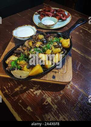 Baked golden potato wedges served with wild mushrooms in black cast iron frying pan, accompanied by white sour cream and fried sausages on old brown w - Stock Photo