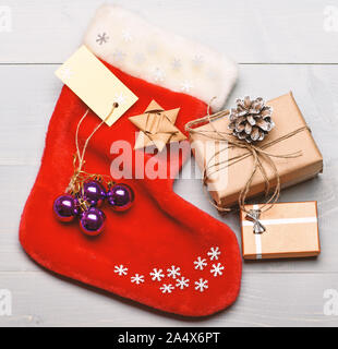 Attributes of christmas. Santa stocking with christmas gift box. Christmas decorative sock light background top view. Christmas stocking sock shaped bag fill with presents. Keep family traditions. - Stock Photo