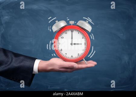 A male hand holds palm up a large red alarm clock with white sound wave lines on blue background. - Stock Photo