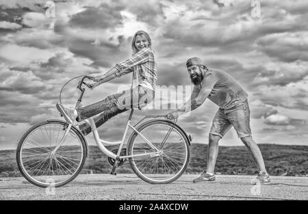 Woman rides bicycle sky background. Man helps keep balance and ride bike. How to learn to ride bike as adult. Girl cycling while boyfriend support her. Cycling technique. Learn cycling with support. - Stock Photo