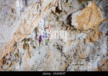 Young female climber resting while sitting on calanet. Woman climber smiling and looking at camera. Challenging route on overhanging cliff. - Stock Photo