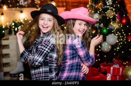 Preparing to Christmas. little girls sisters. Christmas shopping. cowgirl children. Xmas tree. Holiday shopping. Little girl in cowboy hat. Shopping day. Christmas time. Shopping sale. Happy new year. - Stock Photo