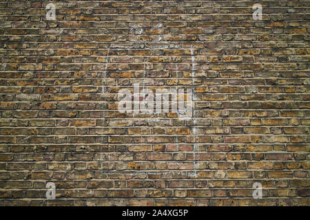 Head-on view of an old yellow and brown brick wall with a doorway drawn on it in chalk. - Stock Photo