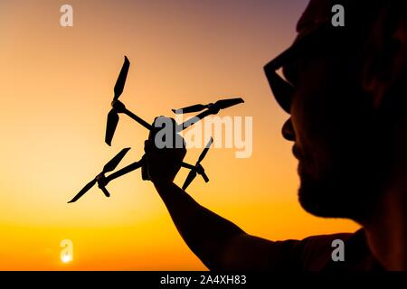 Men Flying Small Drone During Sunset. Aircraft in a Hand. Industrial Theme. - Stock Photo