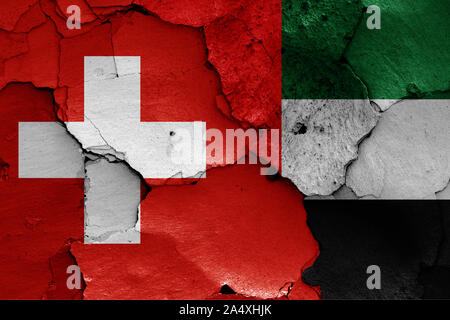 flags of Switzerland and United Arab Emirates painted on cracked wall - Stock Photo