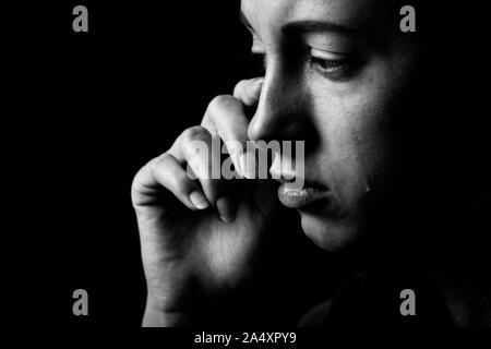 sad woman crying on black background, looking down, closeup portrait, monochrome