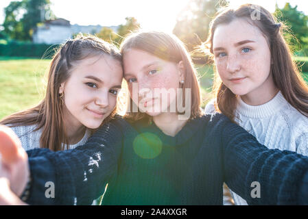 Three girls schoolgirls girlfriends, close-up, taking pictures themselves camera phone. Video recording, video call, online application Internet. In - Stock Photo