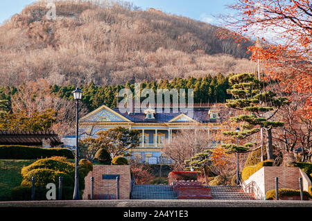 DEC 2, 2018 Hakodate, JAPAN - Colourful Old Hakodate Public Hall European style building among big trees in Motomachi with Mount Hakodate in backgroun