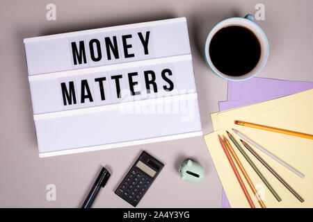 Money Matters. Finances, revenue, economy and profit concept. White lightbox on a gray office desk