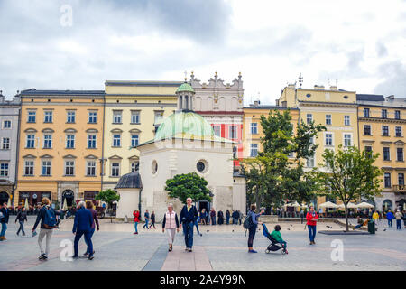 Tourists enjoying their time at Krakow's Main Square (Rynek Glowny) located at center of the Old Town district in Lesser, Poland - Stock Photo
