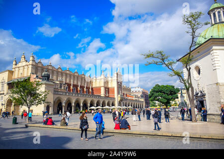 Tourists enjoying their time at Krakow's Cloth Hall located at the center of main market square (Main Square) in the Krakow Old Town, Poland - Stock Photo