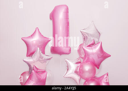 Decoration for 1 years birthday, anniversary. Bunch of gel-shaped pink balloons and stars on pink background. Symbol of happy childhood, first - Stock Photo