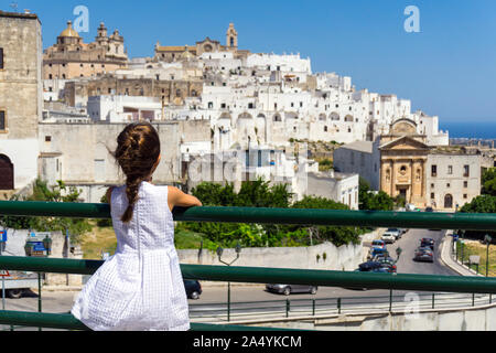 Italy, Apulia, Ostuni, little girl looking old town cityscape - Stock Photo