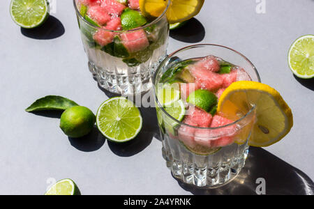 Two glasses with a cooling drink with sour lime and sweet watermelon on a dark background with hard shadows and back light, decorated with lemon slice - Stock Photo