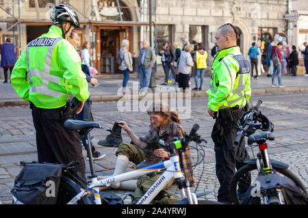 LVIV, UKRAINE - OCT 16, 2019: police Men On Bicycles follows the public order in the centre of the Europian city. In the spotlight a person with an un - Stock Photo