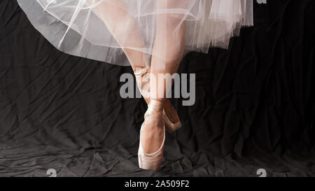 Close-up of dancing legs of ballerina wearing white pointe on a black background. Ballet dancer and practice concept background - Stock Photo