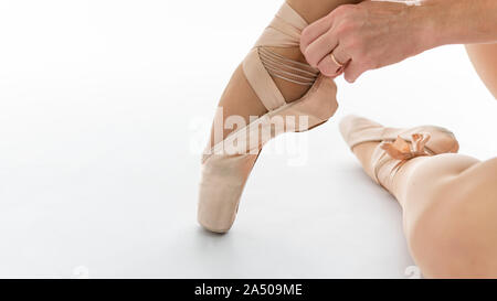 Close-up of beautiful legs of young ballerina who puts on pointe shoes on white background. Ballet dancer and practice concept background - Stock Photo