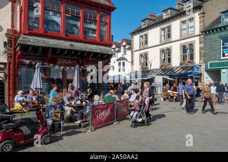 People tourists visitors sitting outside cafe in summer Market Square Keswick Cumbria England UK United Kingdom GB Great Britain - Stock Photo