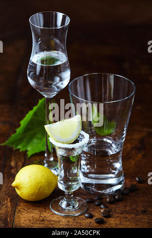High angle close-up of white grappa shots in three different transparent glasses, decorated with lemon, coffee beans and green grape leaves on dark la