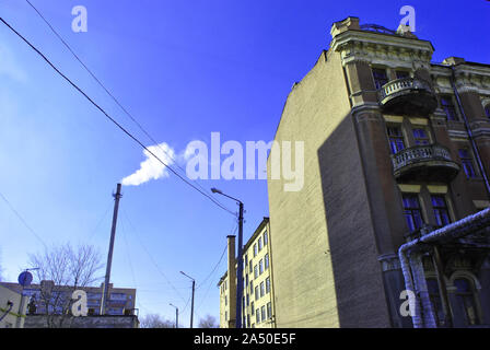 Old pipe with smoke, residential brick buildings corners with windows and wires on winter bright blue sky background, view from ground on top - Stock Photo