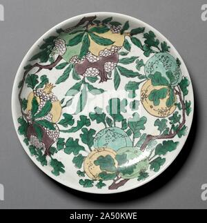 "Dish with Dragons, Pomegranates, and Peaches, 1662-1722. Various techniques are applied to the decoration of susancai or ""plain three-colour"" ware. The hidden dragons are incised, over which are painted decoration of fruit and flower sprays outlined with black pigment and coloured with yellow, green, turquoise, and purplish brown enamels. The ground is filled with ivory enamel over unglazed clay. - Stock Photo"