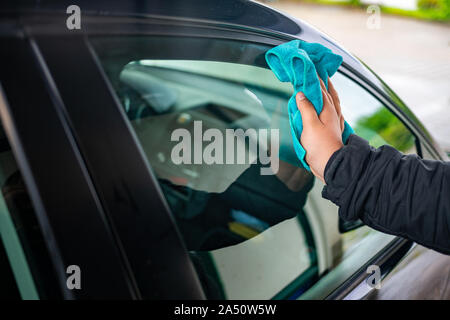 A person polishes the window on a car with a leather cloth - Stock Photo