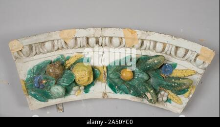 Fragment, c. 1900-1910. In this work, originally forming an altarpiece, the graceful figures are coloured with vitreous glazes, essentially a substitute for the more costly carved marble. The two shields below bear the arms of the Borgherini Family, and probably graced a chapel in Florence owned or endowed by this family. The artist, Benedetto Buglioni, was a sculptor of stature in early sixteenth century Florence. He learned the technique of glazed terracotta sculpture from the Della Robbia Family, examples of whose work may be seen nearby in this gallery. - Stock Photo