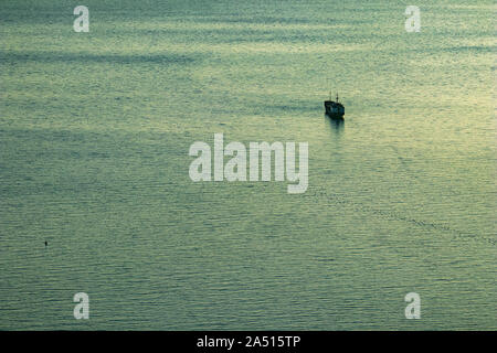 Silhouette of one container freight cargo ship sailing away, in the blue hour sea water near the town of Saranda, Albania. Minimalism picture
