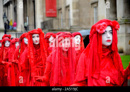 London, UK. 17th October 2019. Despite a city-wide ban on protests, member of Extinction Rebellion's Red Brigade walk slowly from Trafalgar Square to Covent Garden