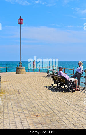 People sitting and relaxing on the banjo pier at Swanage in the summer sunshine. Lone young woman at end of pier. - Stock Photo