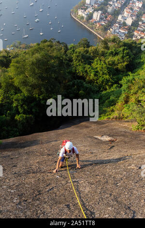 Man rock climbing in Morro da Urca near the Sugar Loaf Mountain, Rio de Janeiro, Brazil - Stock Photo